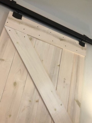 close up of a diy barn door that is white washed with bronze hardware