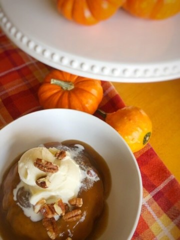 pumpkin pudding cake in a white bowl with fall decor in the background