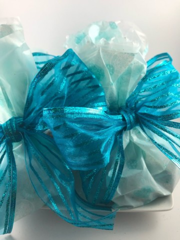 wrapped edible food gifts in blue packaging with a blue bow