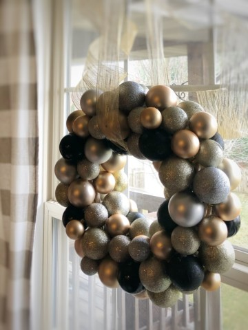 diy new years wreath made with silver, gold, and black Christmas ornaments with a beautiful gold ribbon