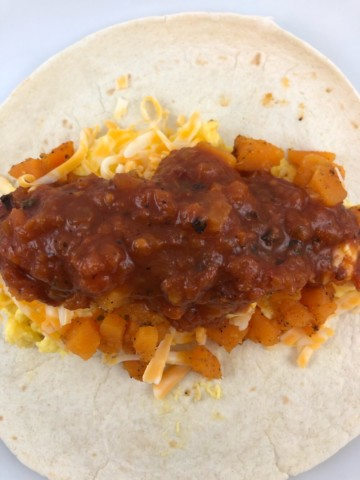 a closeup of a southwest breakfast burrito with sweet potatoes and salsa in an unwrapped flour tortilla