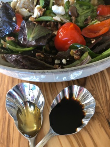 a salad with an assortment of Mediterranean condiments and a side of olive oil and balsamic dressing