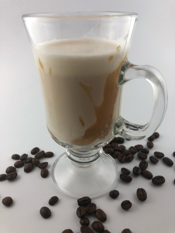 homemade affogato in a glass dessert coffee cup surrounded by coffee beans