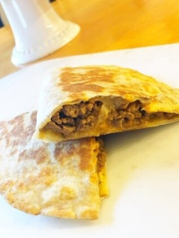 Cheeseburger Quesadillas cut in half revealing the beef loaded inside.