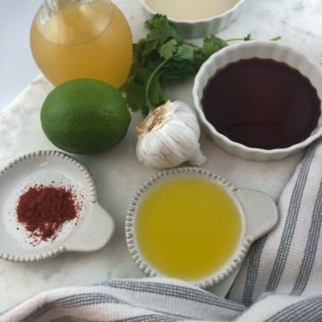 all of the ingredients for a marinade, like garlic, olive oil, spices, lime, soy sauce, vinegar, and orange juice