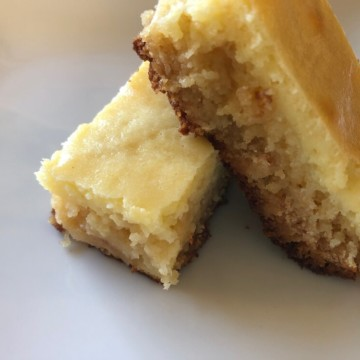 white chocolate blondies with a layer of cheesecake, the bars are stacked so you can see the layers.