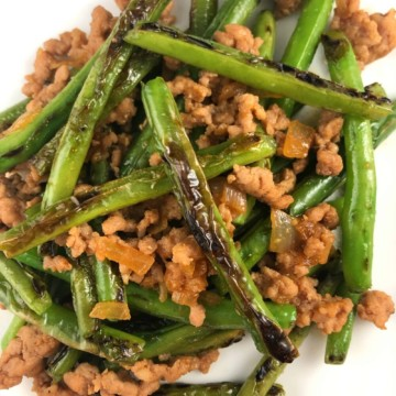 Asian spicy pork with charred green beans on a white plate