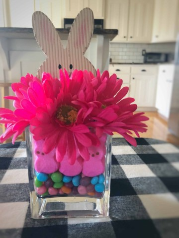 Easy diy easter centerpiece using cheap dollar store finds like peeps, candies, flowers, and a bunny