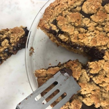 Oatmeal cookie dough fudge pie with a slice taken out in a pie plate