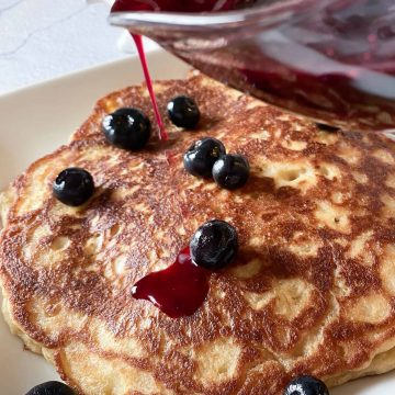 easy oatmeal pancakes with a homemade blueberry pancake syrup being poured over the top