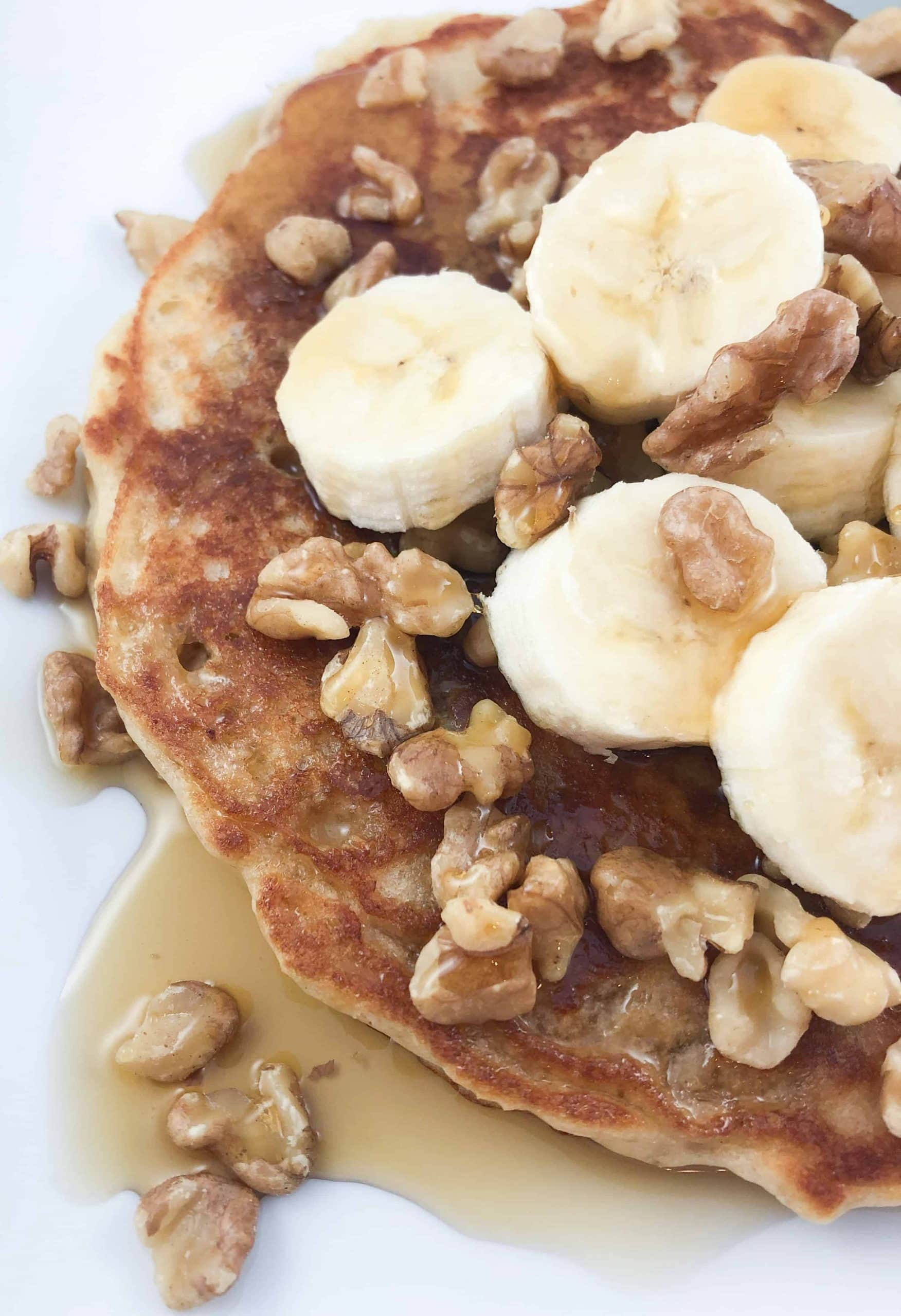 healthy oatmeal pancakes with banana nut toppings and pure maple syrup