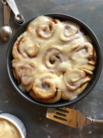 homemade cinnamon rolls with vanilla cream frosting on top surrounded by assorted baking utensils