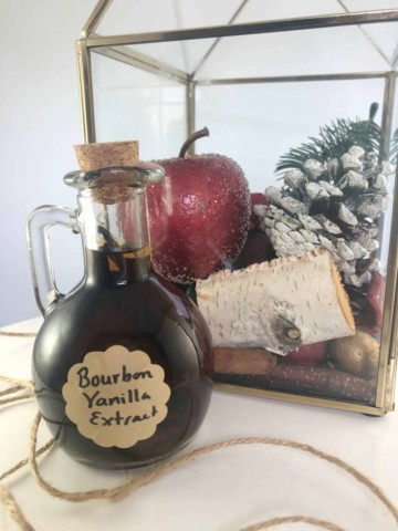 homemade vanilla extract in a decorative bottle with cute little Christmas decor in the background