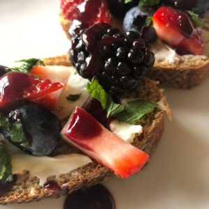 Multigrain toast with Greek cream cheese, berries, mint, and a berry sauce