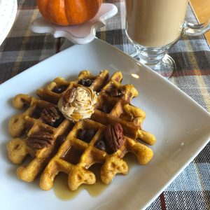 delicious buttermilk pumpkin waffles with cinnamon butter, pecans, chocolate chips, and maple syrup