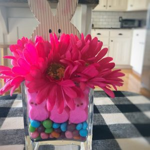 Diy Easter centerpiece with vibrant pink flowers, peeps, and pastel candies