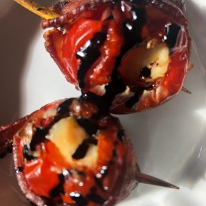 peppadew peppers stuffed with cream cheese, wrapped in bacon, with a balsamic reduction