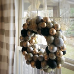 Diy New Years Wreath made with Christmas ornaments in shades of black, gold, and silver