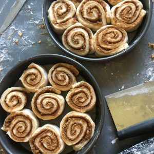 unbaked cinnamon rolls in round baking pans with flour and and brown sugar sprinkled around the table