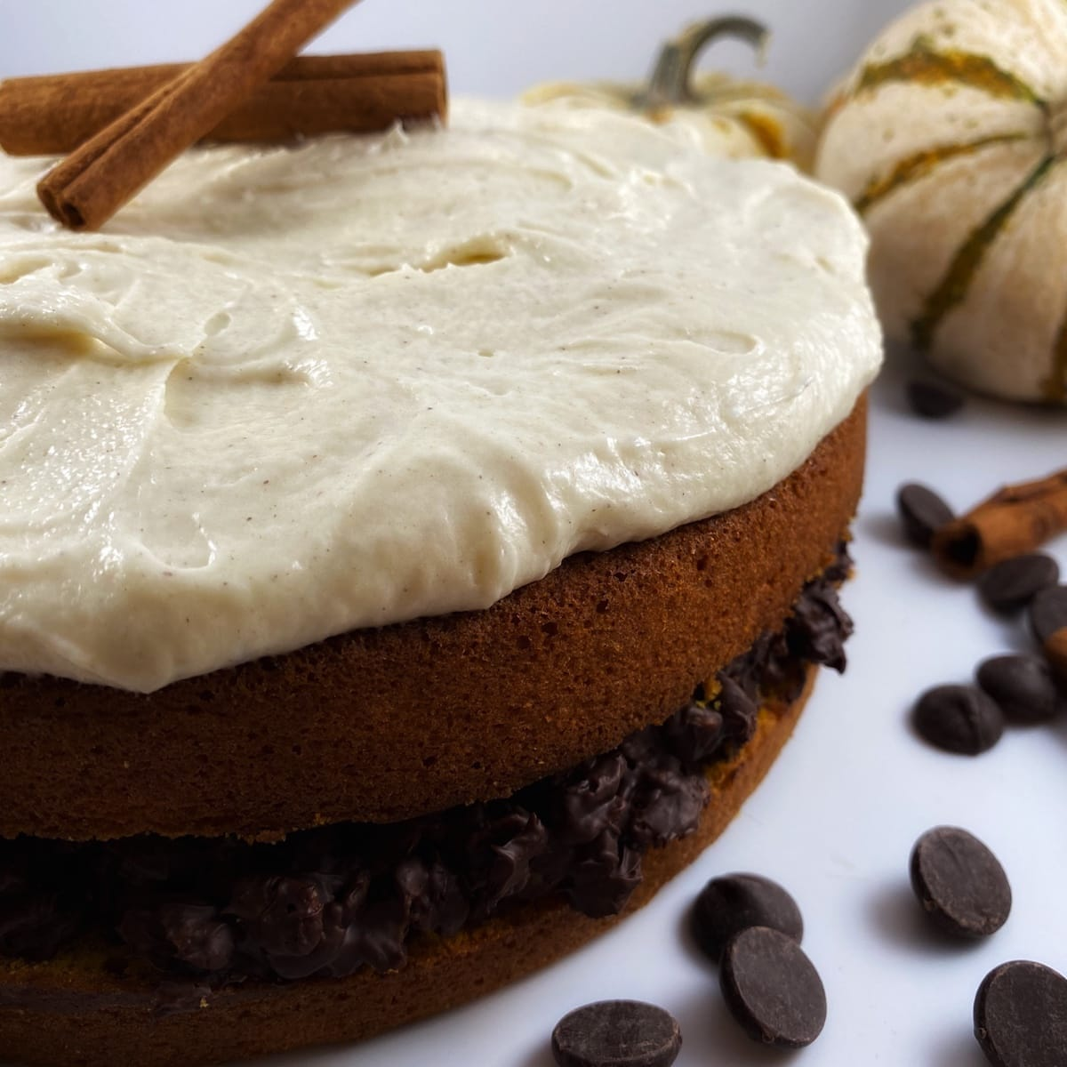 Pumpkin cake with pumpkin spice frosting and  a hazelnut crunch filling  that is garnished with cinnamon sticks and surrounded by pumpkins,  chocolate chips, and cinnamon sticks.