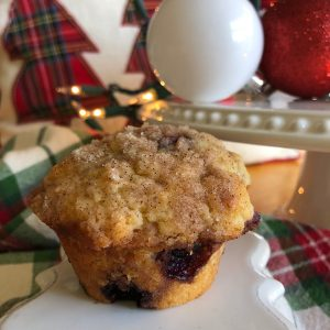 A blueberry muffin with streusel topping with Christmas decorations in the background