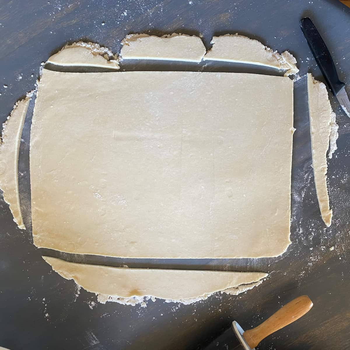 Rolled out puff pastry dough that has been trimmed into a rectangle.