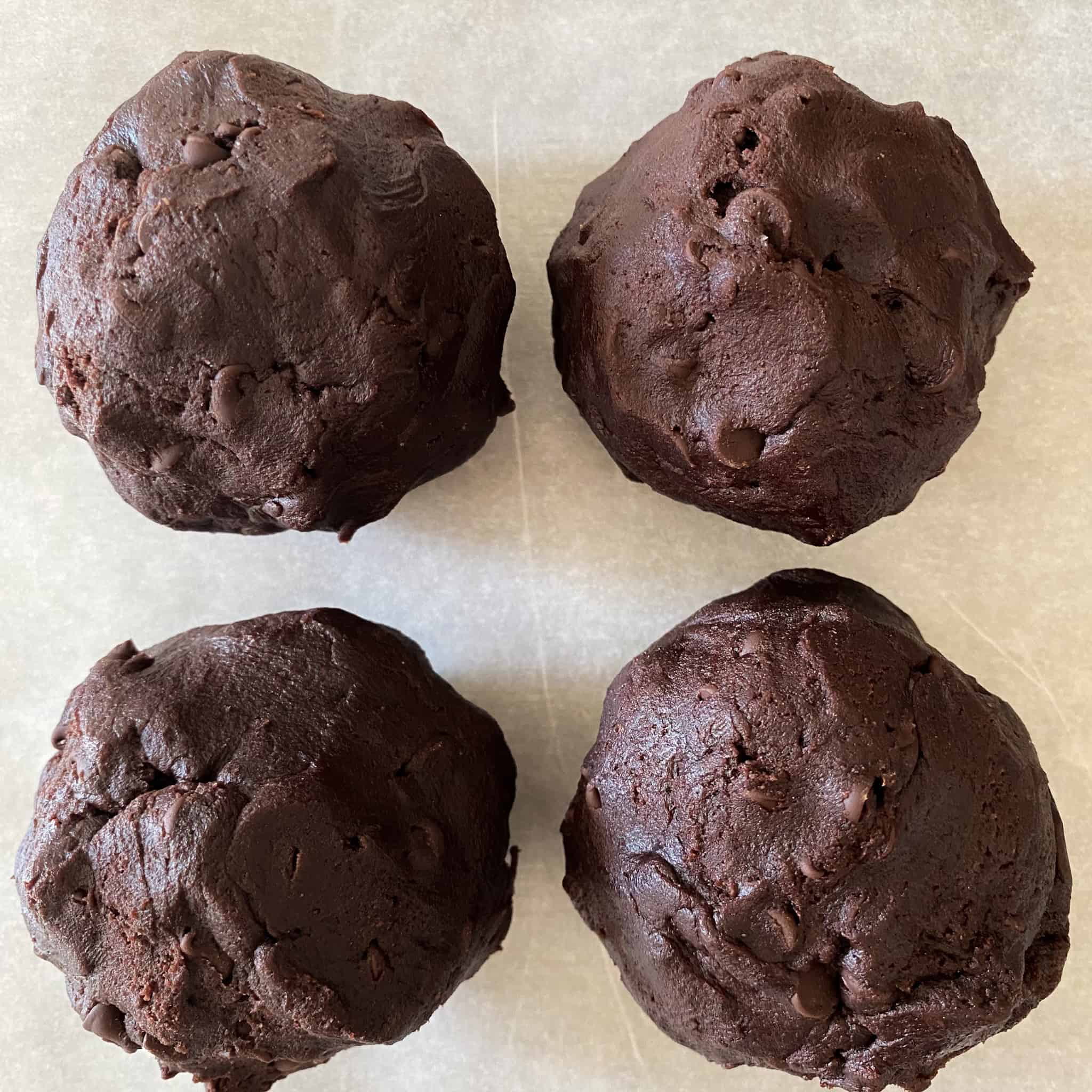 Four large dark chocolate dough balls on parchment paper