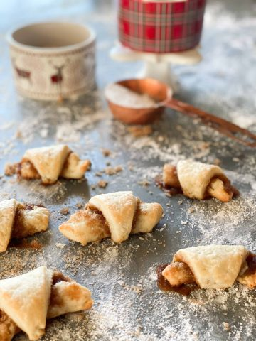 Rugelach, a polish cookie surrounded by powdered sugar and brown sugar with Christmas ramekins in the background