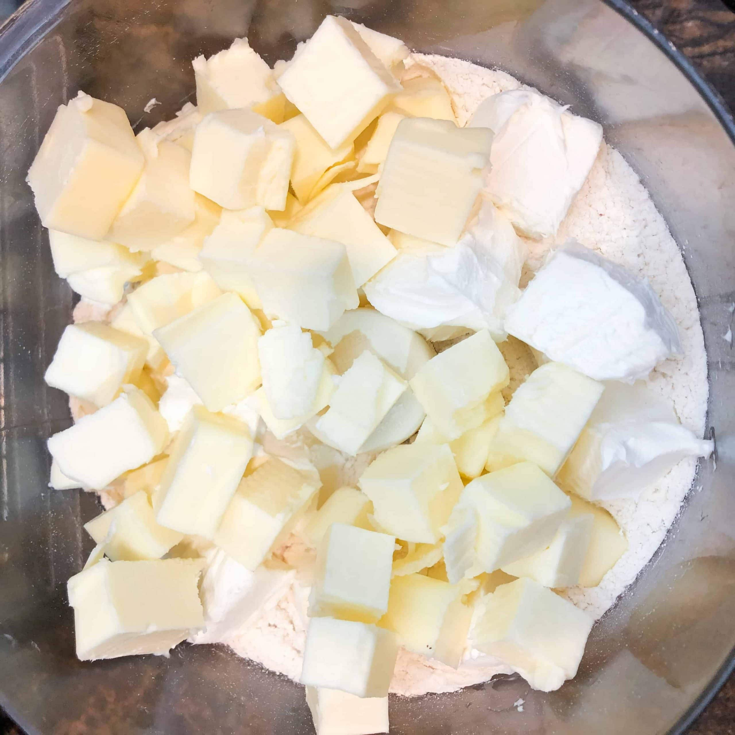 Cubed butter and cream cheese that has been added to a food processor with flour and salt to make a rugelach dough.