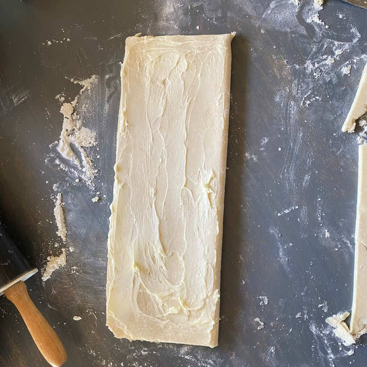 Folded puff pastry dough with softened butter spread on top for laminating