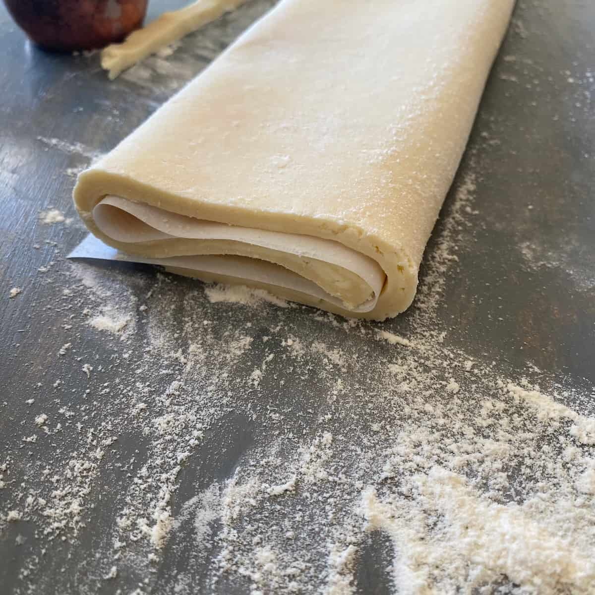 Puff pastry dough that has a layer of parchment paper in between each layer and is ready for storing.