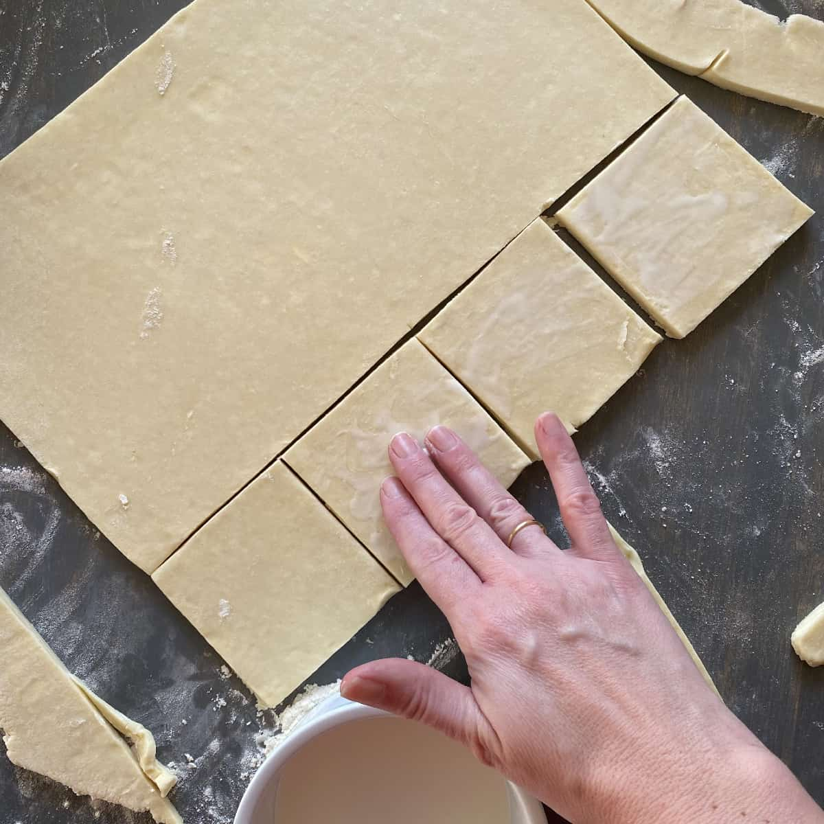 homemade puff pastry that has been cut into squares and brushed with cream for baking