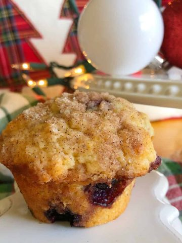a blueberry streusel muffin with Christmas decor in the background