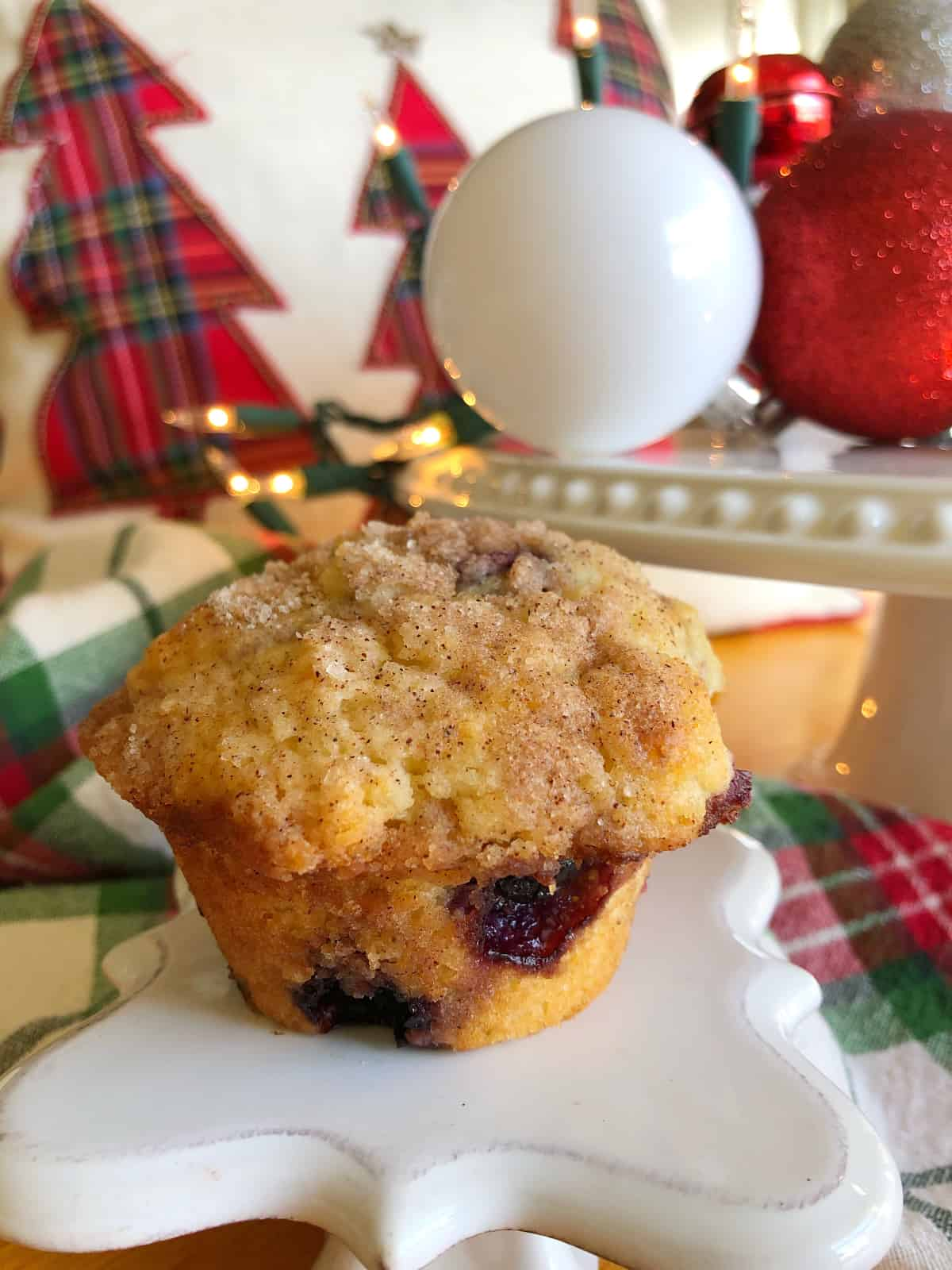 Christmas morning blueberry streusel muffin with the muffin on a decorative pedestal with Christmas decor in the background