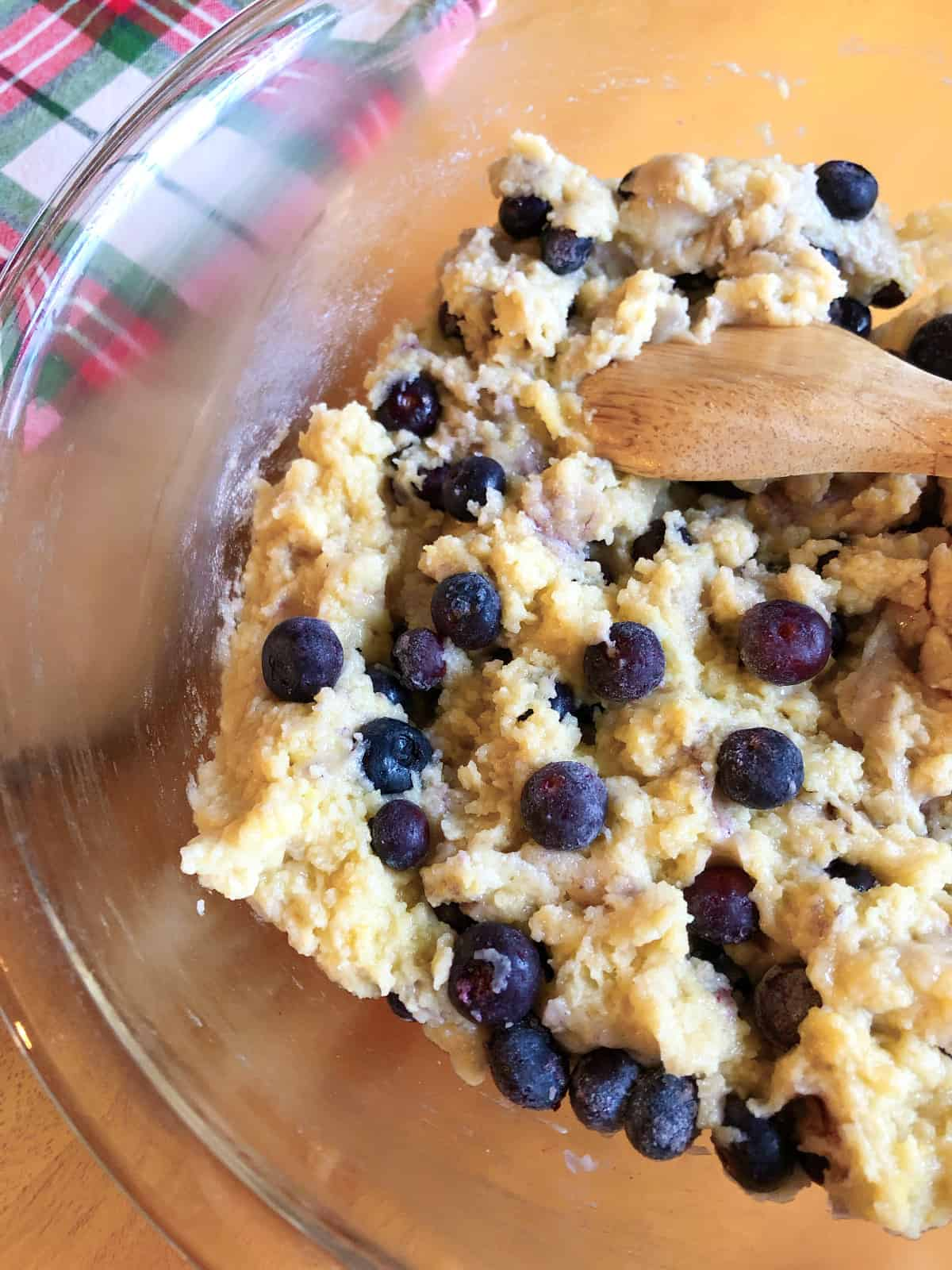 a thick blueberry streusel muffin batter with loads of blueberries, Christmas napkin in the background