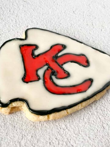 homemade chiefs sugar cookie in the shape of an arrowhead (using a christmas tree cookie cutter to make the shape) and designed with the Chiefs logo