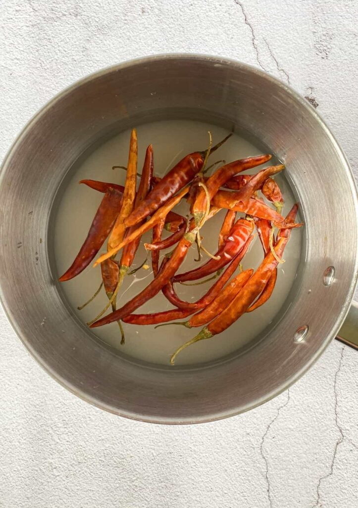 dried chili pods in simple syrup in a pot