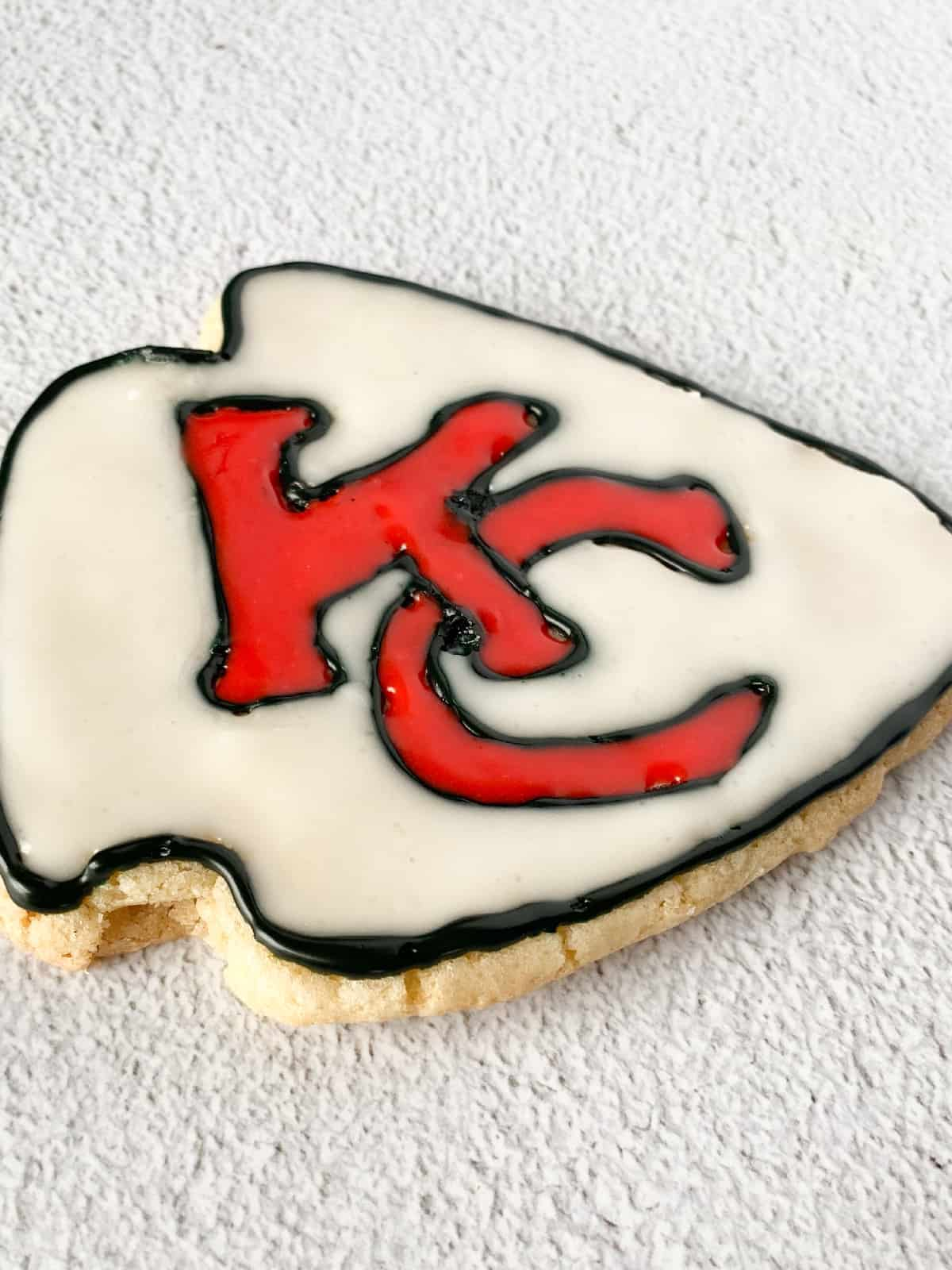 a chiefs sugar cookie made from a Christmas tree cookie cutter with the chiefs logo on top