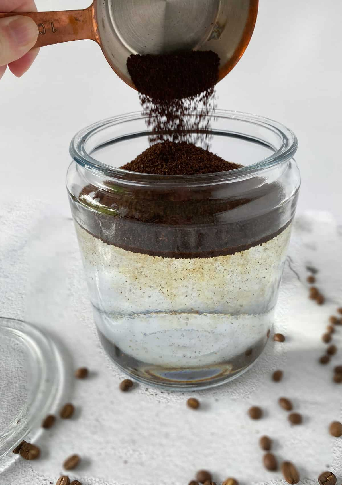 coffee grounds being poured into a glass jar of water for homemade cold brew coffee