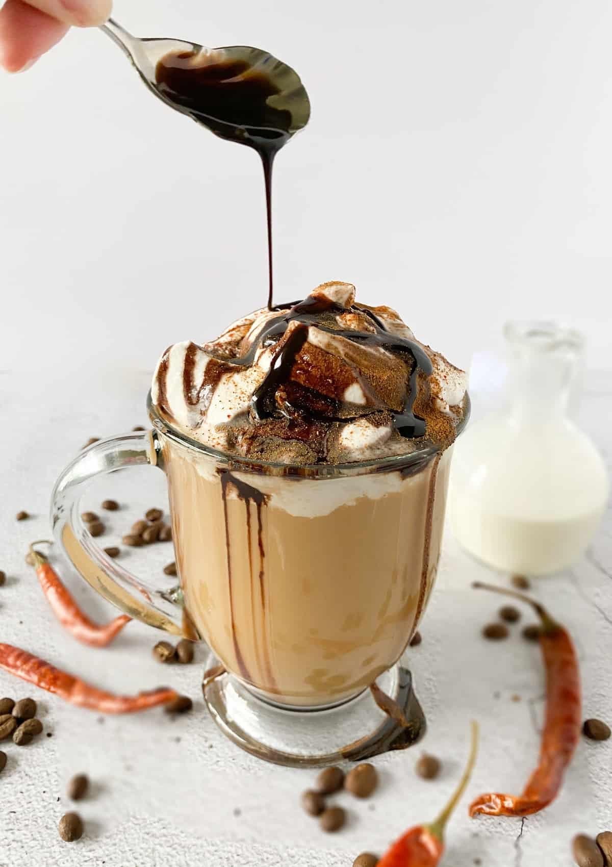 Spicy Cowgirl Coffee, a dessert coffee in a clear mug with whipped cream and chocolate sauce being poured over the top