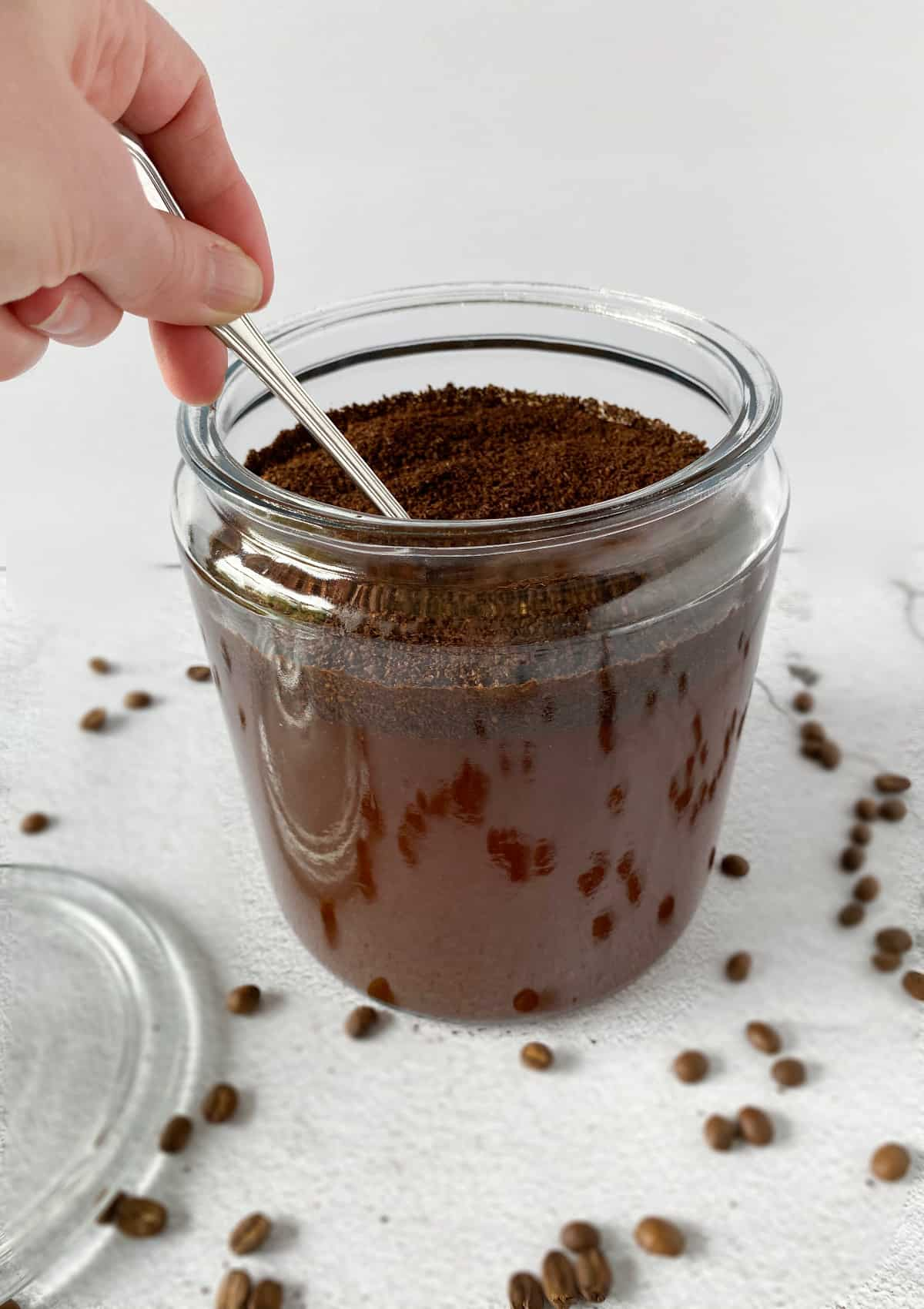 coffee grounds being stirred in a glass jar for homemade cold brew coffee