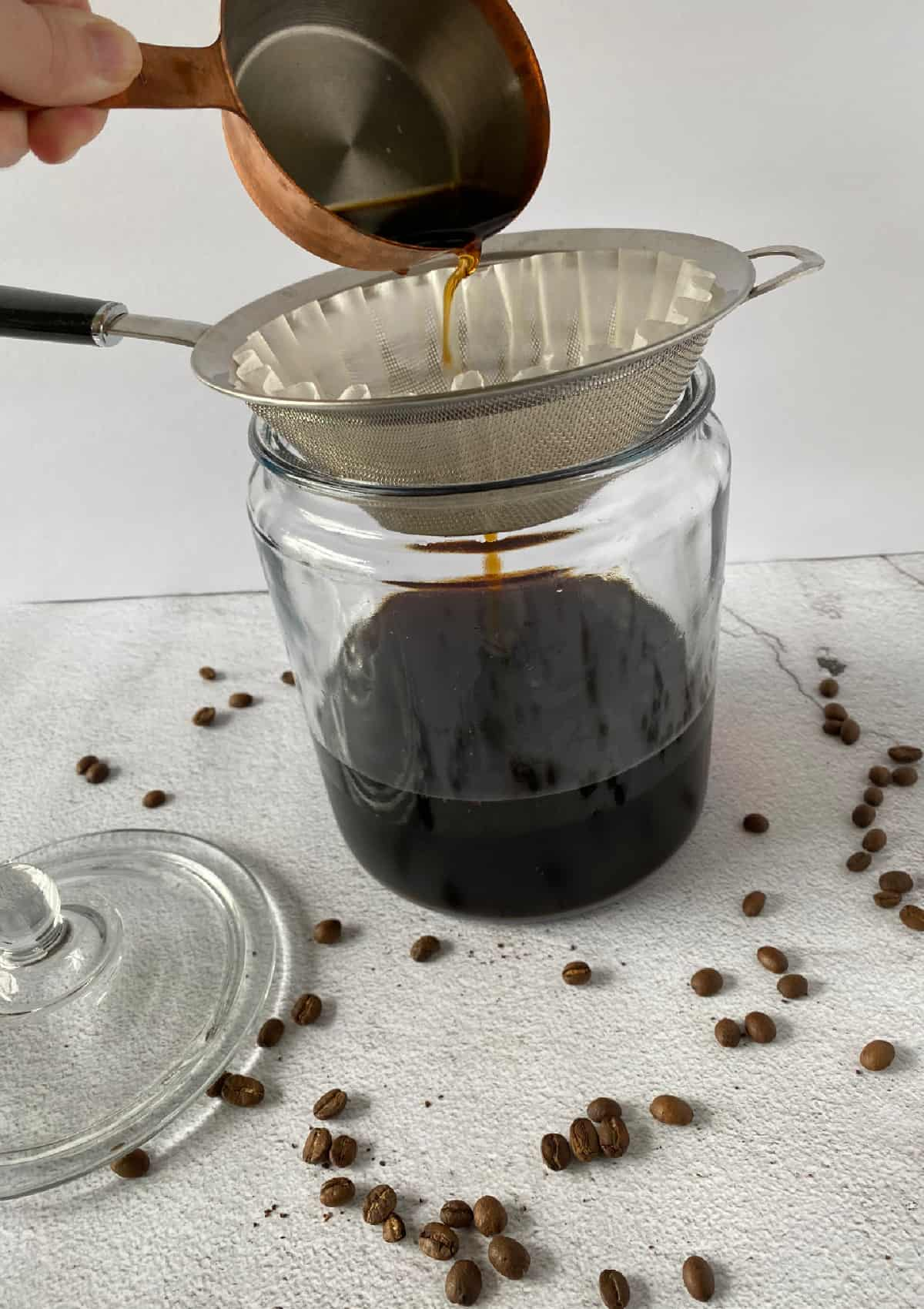 straining coffee grounds through a fine mesh sieve for cold brew coffee
