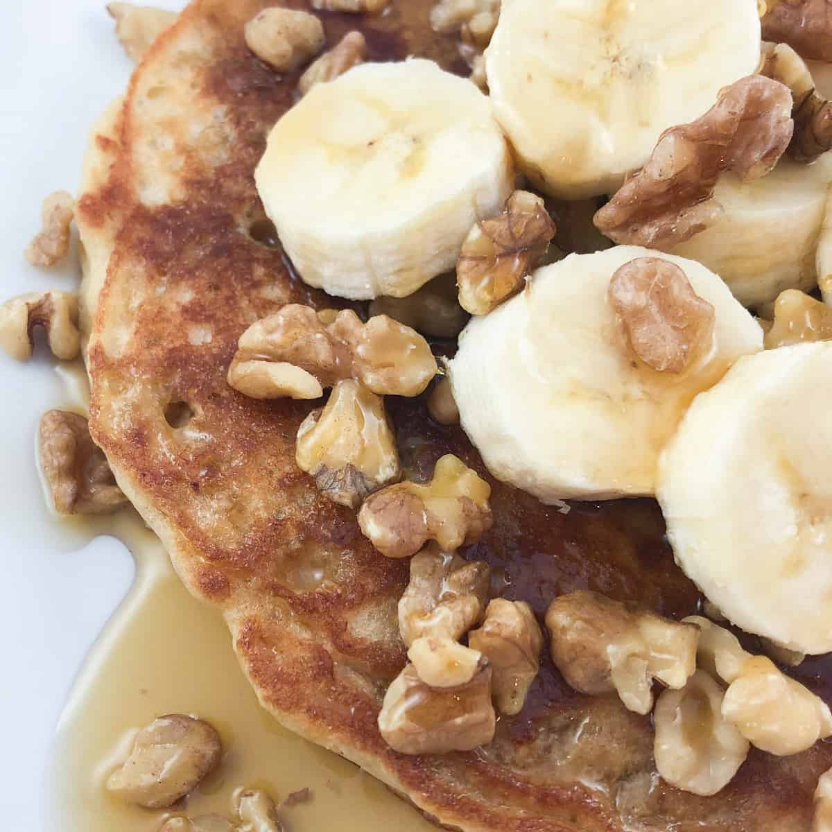 healthy oatmeal buttermilk pancake topped with bananas, walnuts, and maple syrup