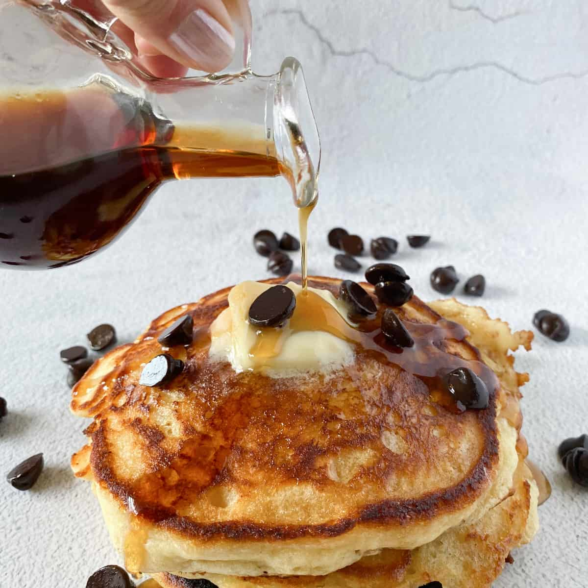 maple syrup being poured over the top of a stack of Missouri Girl Home fluffy olive oil buttermilk pancakes that is topped with butter and chocolate chips