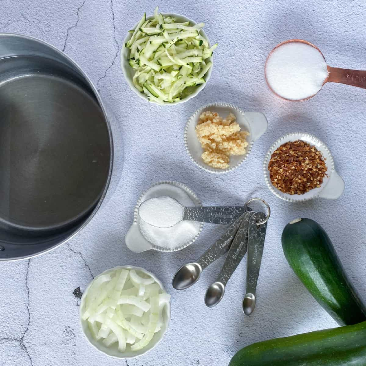 ingredients to make pickles zucchini including zucchini, sugar, salt, garlic, onions, and a pot of water and vinegar.