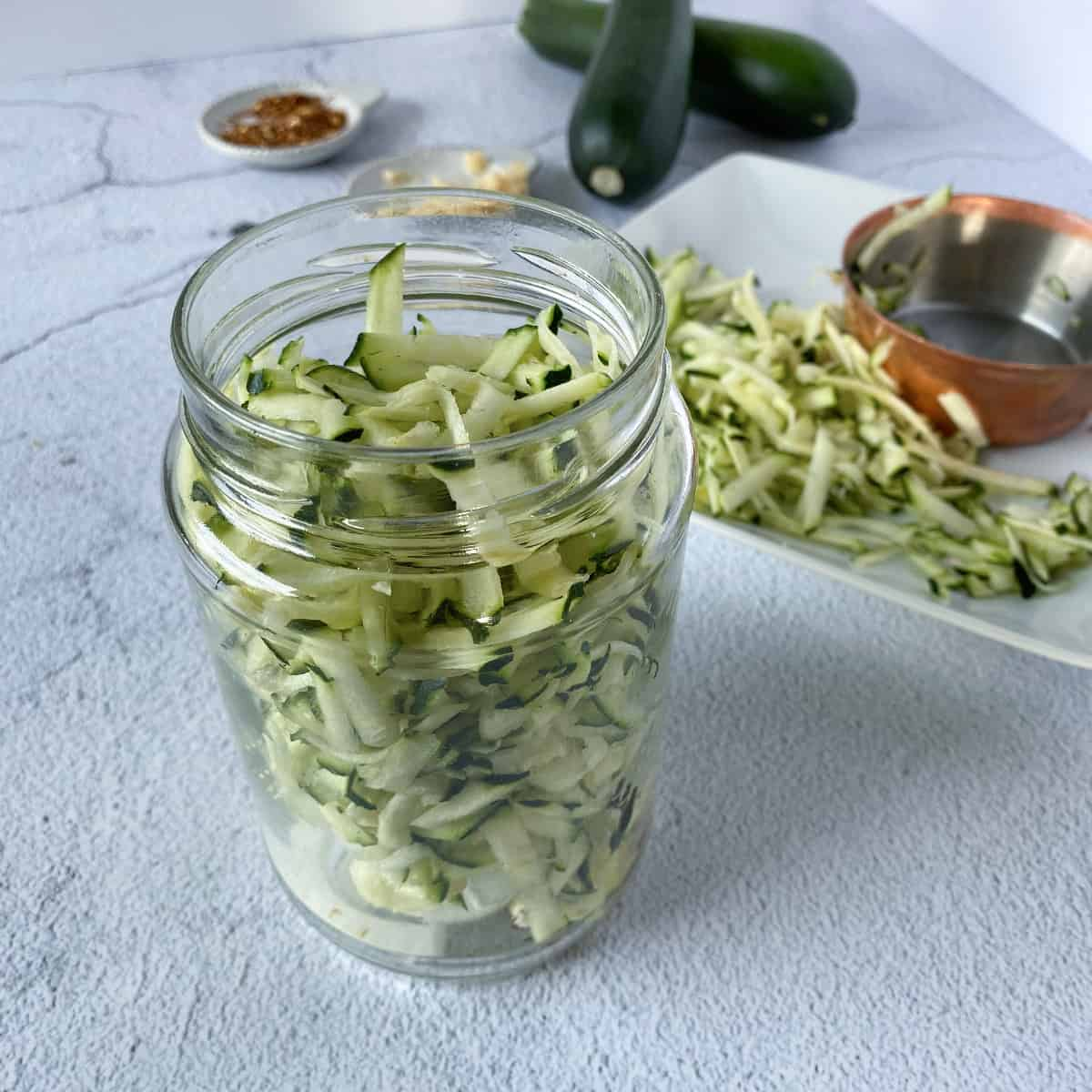 a jar filled with shredded zucchini and other ingredients for pickled zucchini