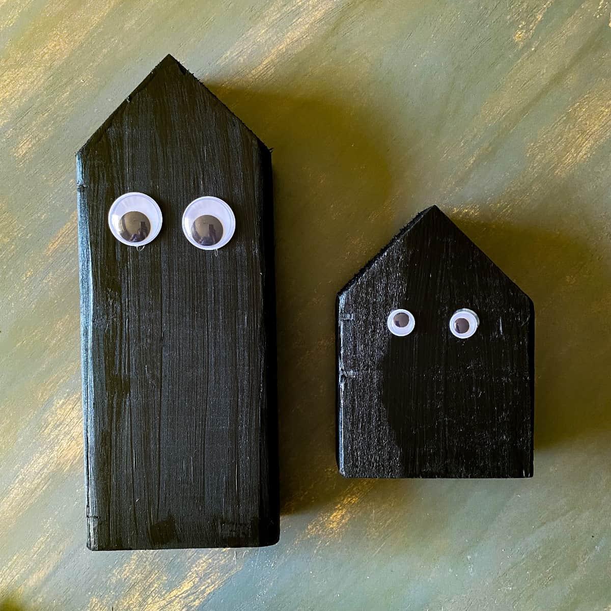 Adding googly eyes to halloween black cat wood block decor.