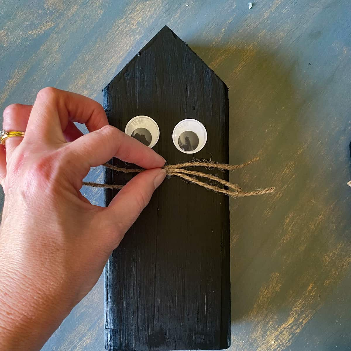 Attaching twine whiskers with hot glue to Halloween black cat wood block decor.