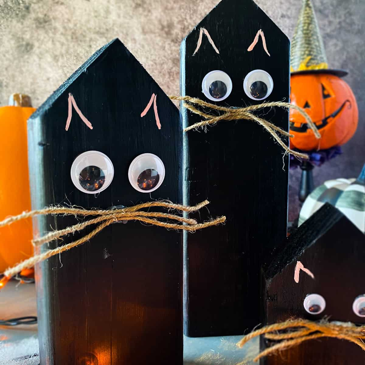 Three Halloween black cat wood block decor with Halloween decorations in the background.