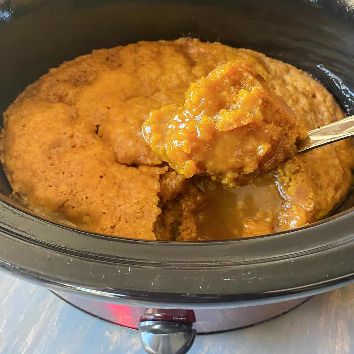 warm crockpot pumpkin cobbler on a spoon showing the pumpkin caramel sauce hiding underneath in the crockpot